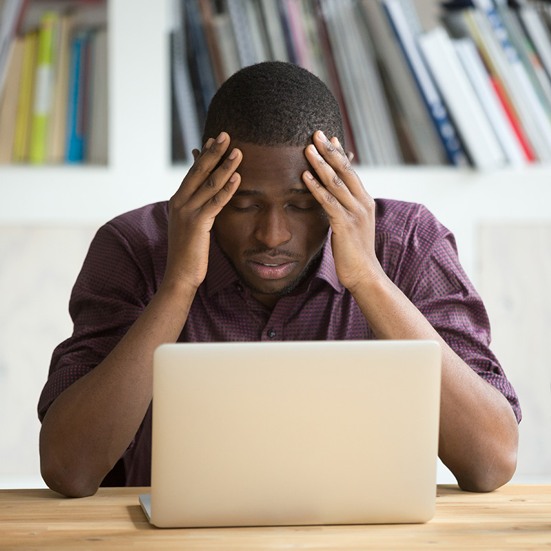 A man is stressed about finances while on his computer