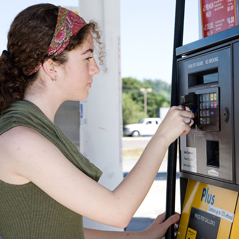 A woman pays for gas at a gas station with a credit card
