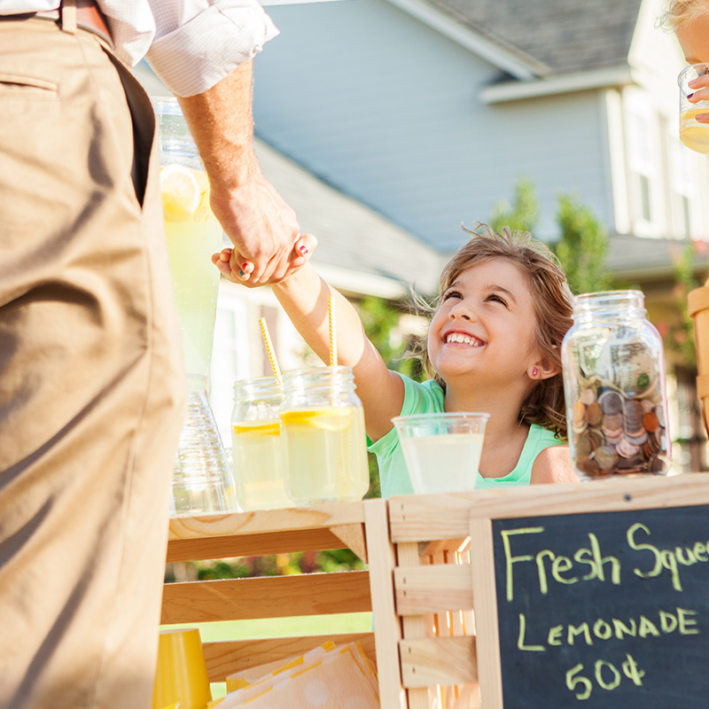 A child sells lemonade at a lemonade stand