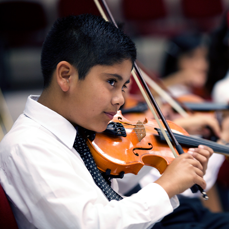 A young boy plays the violin at a concert