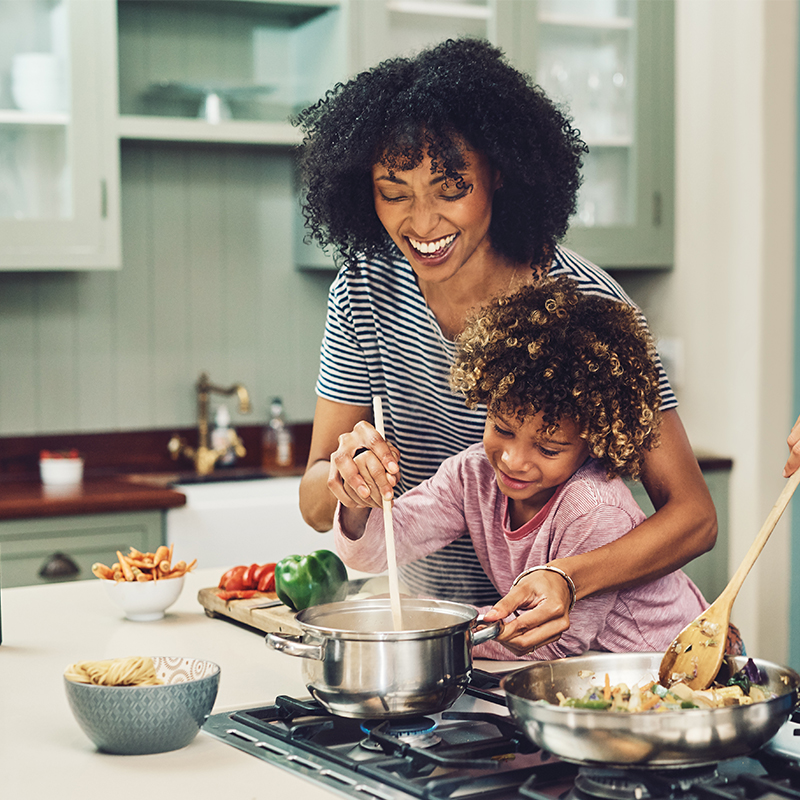 A mother and daughter cook together
