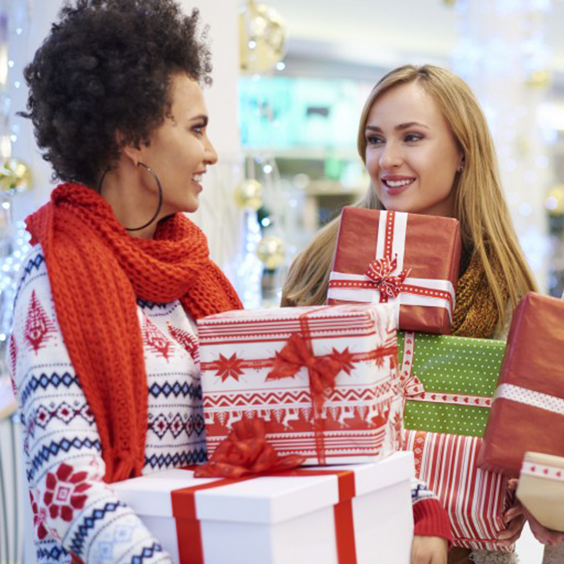 two women holiday shopping holding wrapped gifts
