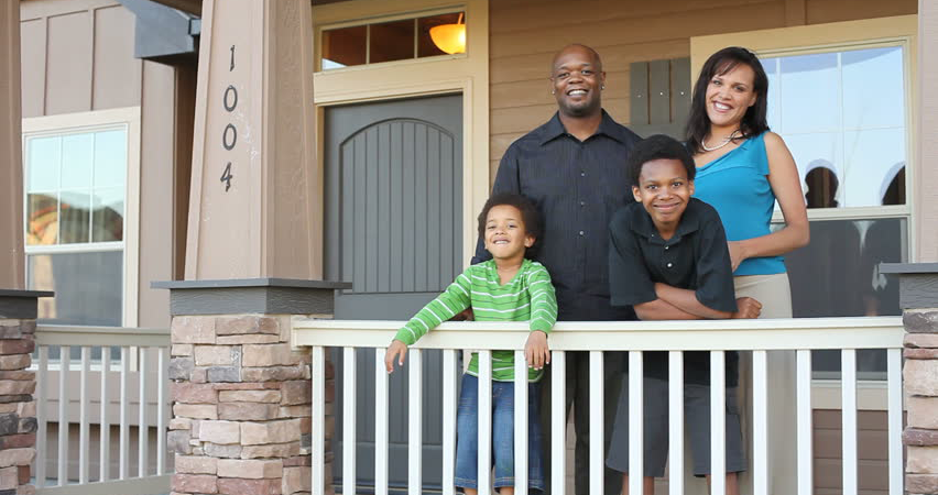 family of four standing on porch of new home